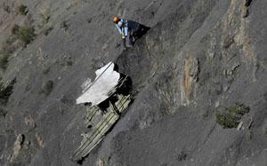 Un vigile del fuoco recupera un pezzo del velivolo - Foto Reuters